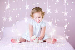 Beautiful toddler girl with curly hair between Christmas lights. Beautiful toddler girl with curly hair wearing a white dress between Christmas lights Stock Photography