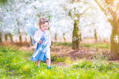 Beautiful toddler girl eating apple in blooming garden Stock Photo