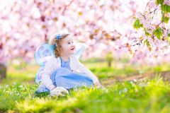 Beautiful toddler girl in fairy costume in fruit garden. Adorable toddler girl with curly hair and flower crown wearing a magic fairy costume with a blue dress Stock Image
