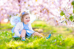 Beautiful toddler girl in fairy costume in fruit garden. Adorable toddler girl with curly hair and flower crown wearing a magic fairy costume with a blue dress Royalty Free Stock Photo