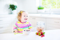Beautiful toddler girl having breakfast drinking juice Royalty Free Stock Image