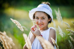 Beautiful toddler girl with long blond hair travels in colorful yellow field Stock Photography