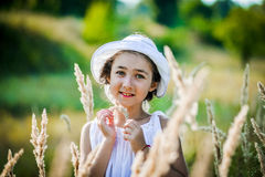 Beautiful toddler girl with long blond hair travels in colorful yellow field Royalty Free Stock Images