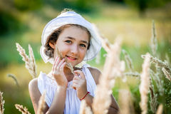 Beautiful toddler girl with long blond hair travels in colorful yellow field Royalty Free Stock Photo