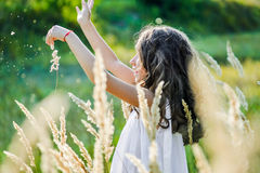 Beautiful toddler girl with long blond hair travels in colorful yellow field Stock Images