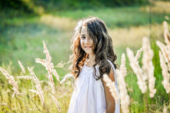 Beautiful toddler girl with long blond hair travels in colorful yellow field Royalty Free Stock Photography