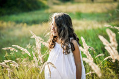 Beautiful toddler girl with long blond hair travels in colorful yellow field. Through high grass Stock Photos