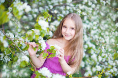 Beautiful toddler girl in pink dress in blossom flowers Royalty Free Stock Photos