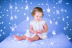 Beautiful toddler girl playing with her toy bear between soft lights in star shape Royalty Free Stock Image