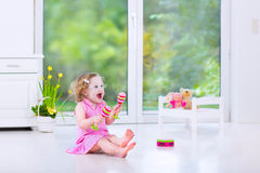 Beautiful toddler girl playing maracas in white room Royalty Free Stock Image