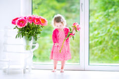 Beautiful toddler girl playing with peony flowers Stock Photo