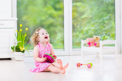 Beautiful toddler girl playing tambourine in white room Royalty Free Stock Photo