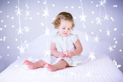 Beautiful toddler girl playing on a white bed between purple Chr Stock Photos