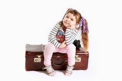 Beautiful toddler girl sitting on retro suitcase Royalty Free Stock Images