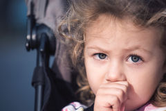 Beautiful toddler girl sucking her thumb in a stroller. Head shot with copy space to the side Royalty Free Stock Photography