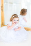 Beautiful toddler girl in white dress next to mirror Stock Photos