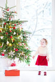 Beautiful toddler girlunder a Christmas tree next  Royalty Free Stock Photo