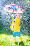 Beautiful toddler with umbrella playing in the rain Royalty Free Stock Photography