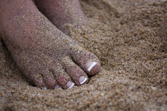 Beautiful toes in the sand. Close up shot of beautiful feet with toes in the sand Royalty Free Stock Photography