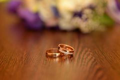 Beautiful toned picture with wedding rings lie on a wooden surface against the background of a bouquet of flowers. Copy space stock photo