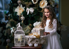 Beautiful toothless girl in  white dress enjoys the gifts Royalty Free Stock Photos