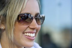 Beautiful Toothy Smile. A beautiful young blond woman bathed in summer sunshine with a big smile and wearing sunglasses which reflect the cafe in which she is Royalty Free Stock Image
