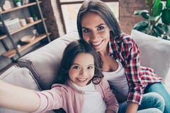 Beautiful with toothy smile mother and her cute daughter are hav. Ing a video conversation with the father, who is abroad now, they are sitting on a sofa at home Stock Photos