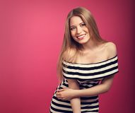 Beautiful toothy smiling positie blond woman in striped dress po. Sing on pink background. Closeup toned bright portrait Royalty Free Stock Photo