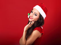 Beautiful toothy smiling woman in santa clause costume with brig. Ht makeup and red lipstick posing on bright red background with empty copy space Royalty Free Stock Photo