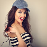Beautiful toothy smiling young make-up model in fashion blue cap. Posing and holding hair on wall background with empty copy space. Long hairstyle and red Royalty Free Stock Photography
