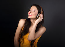 Beautiful toothy smiling young woman in yellow top listening the Stock Photo