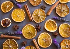 Beautiful top view flat lay arrangement of dry Oranges cinnamon sticks ,star anise and blooming lavender on dark grey background royalty free stock image