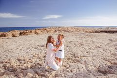 Beautiful top view of young mother playing with daughter with white hat at the sea background. Family vacation. Travel. Female royalty free stock image