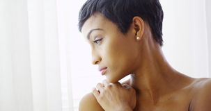 Beautiful topless black woman hugging herself and looking out window stock images