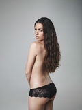 Beautiful topless female model. Topless woman looking over shoulder against grey background. Beautiful and sexy female model posing wearing panties Stock Images