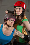 Beautiful and Tough Roller Derby Skaters. Two beautiful tough roller derby skaters with helmets Royalty Free Stock Image