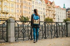 A beautiful tourist girl with a backpack admiring the ancient architecture of Prague in the Czech Republic. Tourism. In Europe Royalty Free Stock Photos