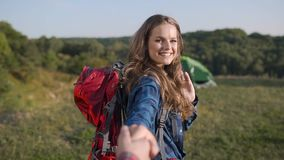 Beautiful tourist girl traveling in nature, holding man`s hand. Beautiful tourist girl with backpack traveling in nature, holding man`s hand on travel vacation stock video footage