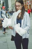 Beautiful tourist girl holds on hands white pigeons. royalty free stock images