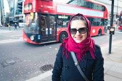 The beautiful tourist girl in London with a red bus in the background. stock photos
