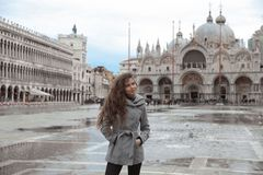 Beautiful tourist girl with long blowing hair in San Marco squar Royalty Free Stock Photography