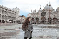 Beautiful tourist girl with long wavy hair in San Marco square i Stock Photos