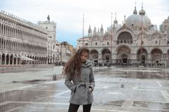 Beautiful tourist girl with long wavy hair in San Marco square i Royalty Free Stock Images