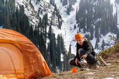 Beautiful tourist girl sits near a tent and heats water in a metal kettle on a gas burner against a background of forest snow-cap. Ped mountains. Leisure Stock Image
