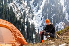 beautiful tourist girl sits near a tent and heats water in a metal kettle on a gas burner against a background of forest snow-cap Stock Photos
