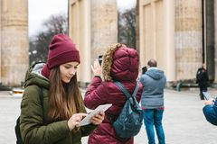 A beautiful tourist girl uses a tablet in the square next to the Brandenburg Gate in Berlin. Nearby unrecognized people take photos of sights. People and stock photos