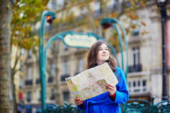 Beautiful tourist in Paris on a fall day, using map Royalty Free Stock Photography