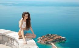 Beautiful tourist relax over Sveti Stefan island in Budva, Montenegro. Sexy brunette traveller girl visiting Adriatic Sea, Balkan Stock Images