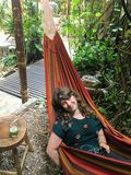Beautiful tourist relaxing in a hammock with a mojito in Flores stock photos
