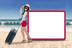Beautiful tourist with signboard at beach Royalty Free Stock Image